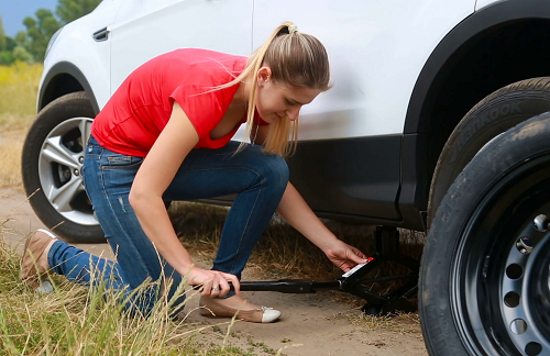 Young Woman Changing Flat Tire